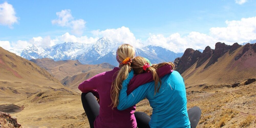 a mother and daughter rest in front of a snowy mountain on the ancascocha trail 7 days