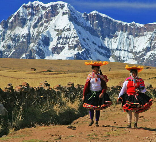 Two women dressed in typical costumes from the background of the Ausangate mountain on the Ausangate trek to Machu Picchu