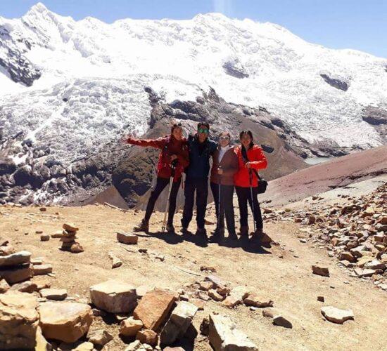 beautiful group photo next to ausangate snowy mountain on ausangate trek and rainbow mountain 4 days